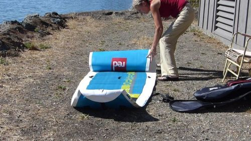 Unrolling the Explorer 12-6 inflatable paddle board.